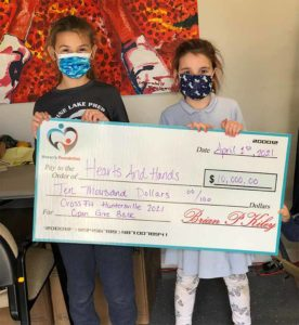 Two young girls holding a check to hearts and hands for 10k